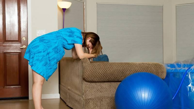 Zwangere vrouw vangt weeën op tijdens thuisbevalling