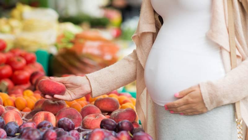 Zwangere vrouw koopt gezond eten op de markt