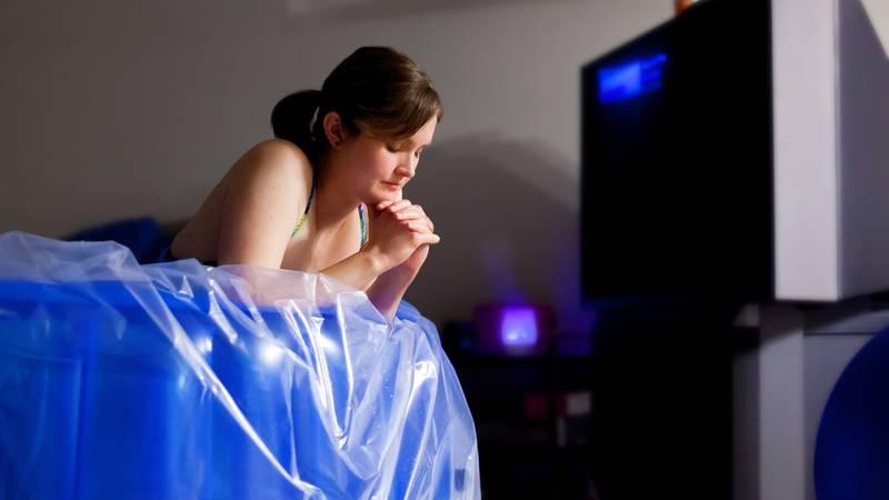 Vrouw tijdens thuisbevalling in bevalbad