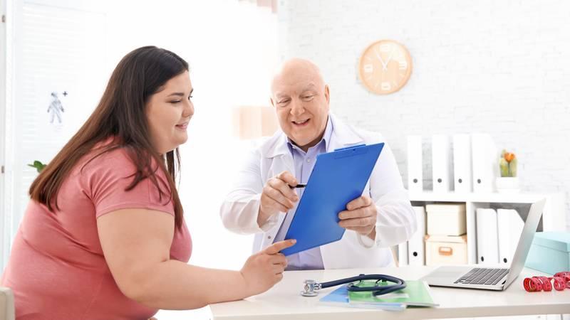 Vrouw met overgewicht in gesprek over gezondheid met arts